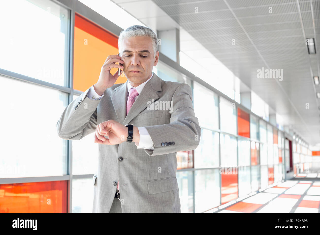 Middle aged businessman checking time while on call at railroad station - Stock Image