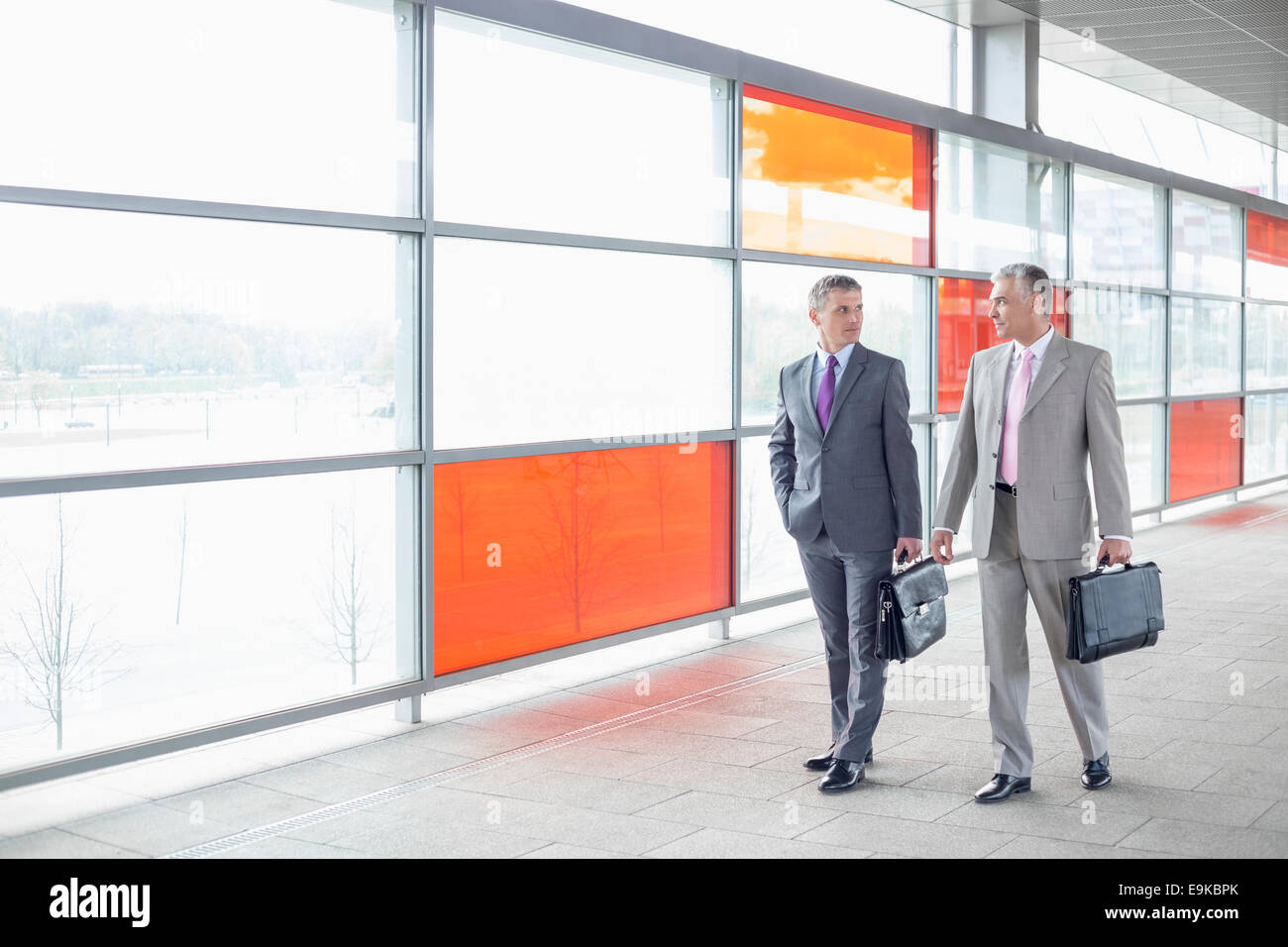 Full length of businessmen with briefcase walking in railroad station - Stock Image