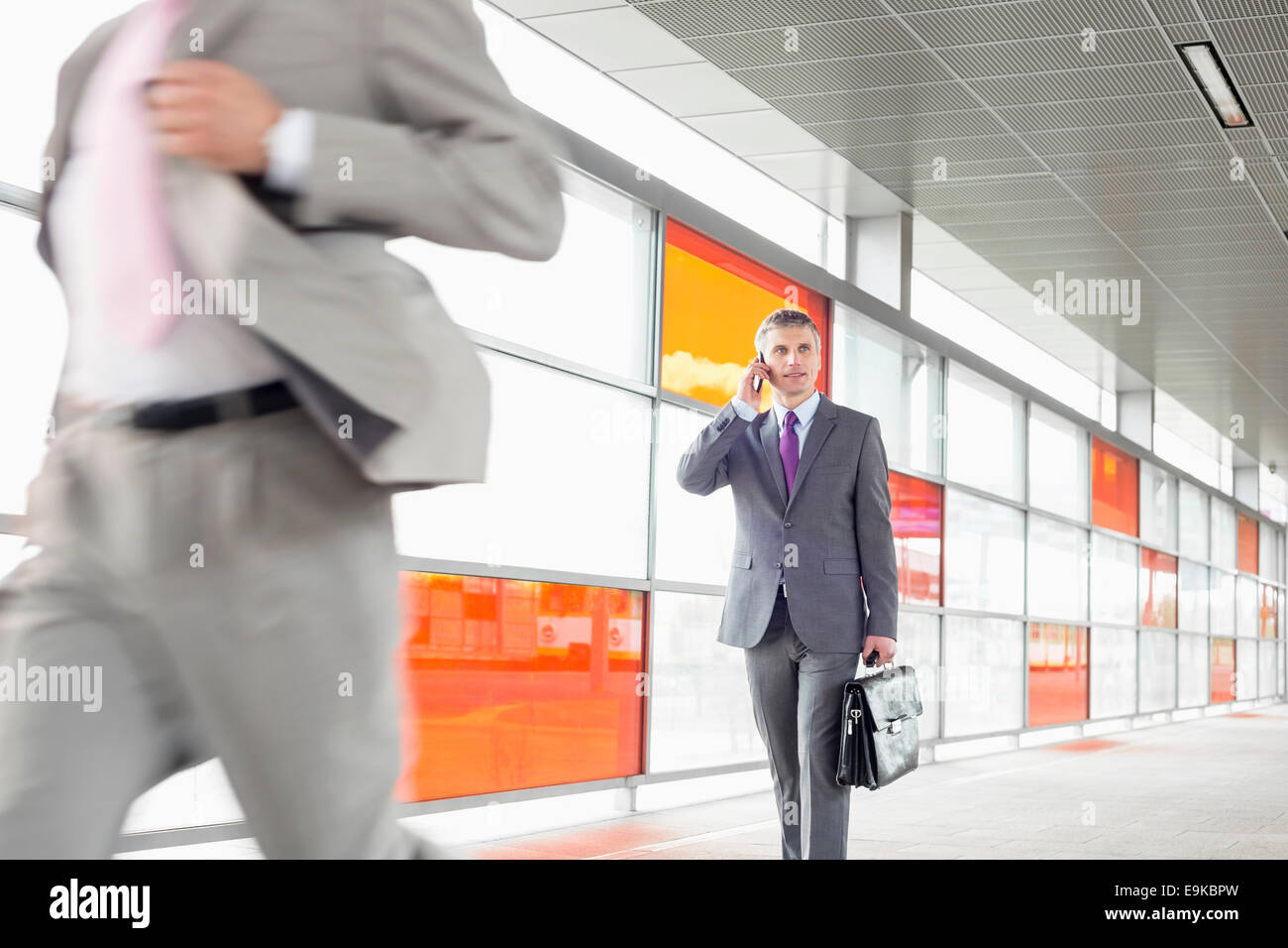 Middle aged businessman on call while walking in railroad station Stock Photo