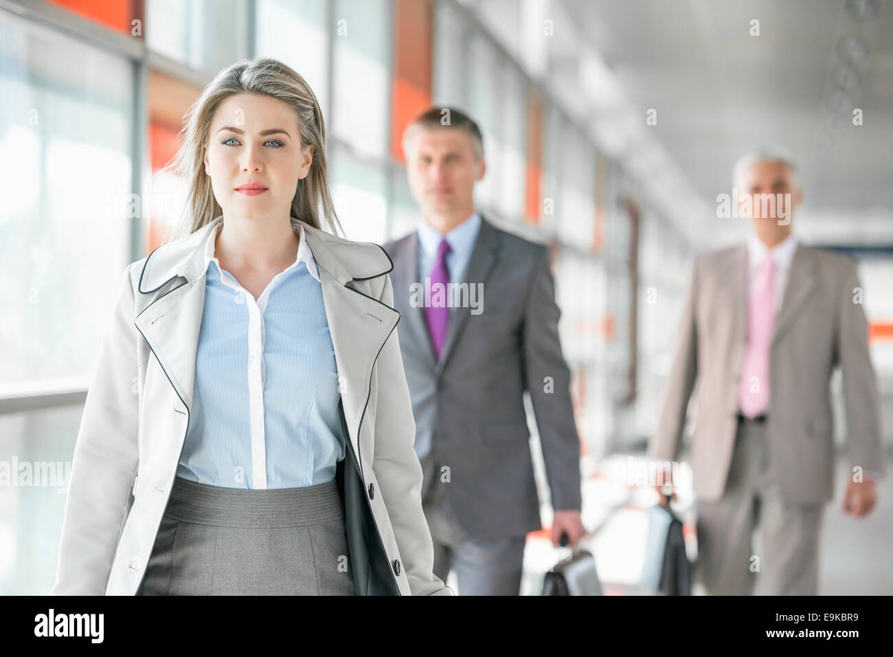 Beautiful young businesswoman walking with male colleagues in background at train platform - Stock Image