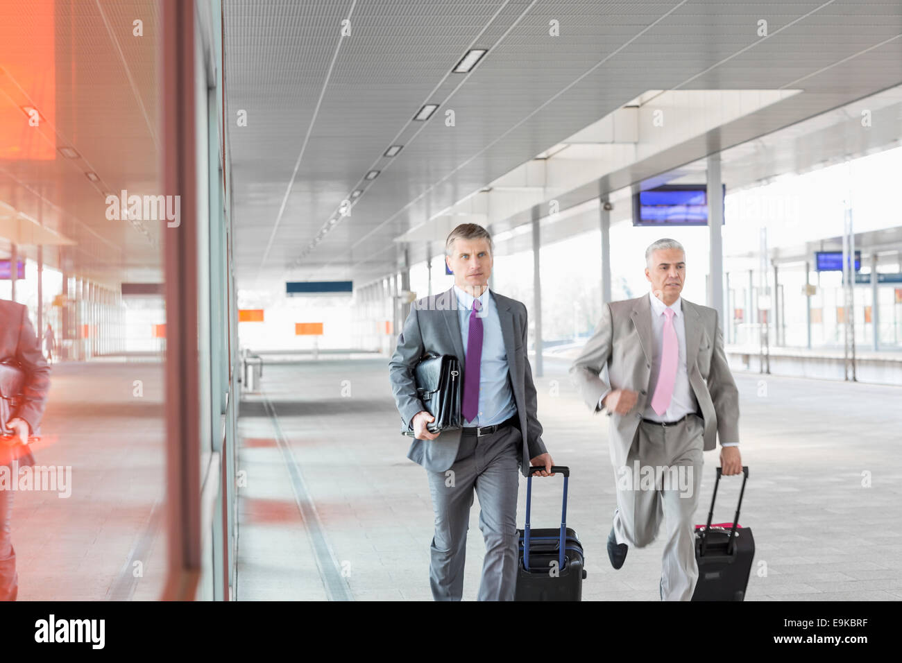 Middle aged businessmen with luggage rushing on railroad platform - Stock Image