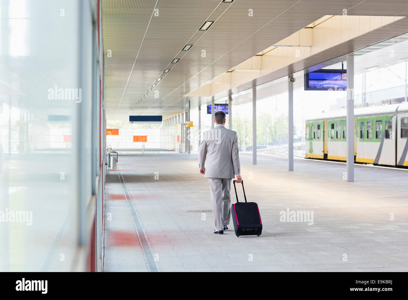 Full length rear view of businessman with luggage walking in railroad platform - Stock Image