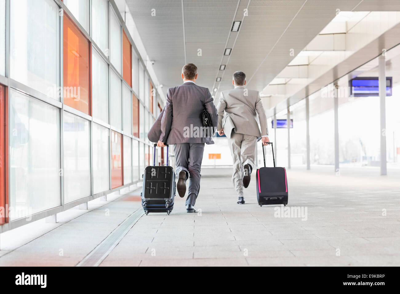 Full length rear view of businessmen with luggage running on railroad platform - Stock Image