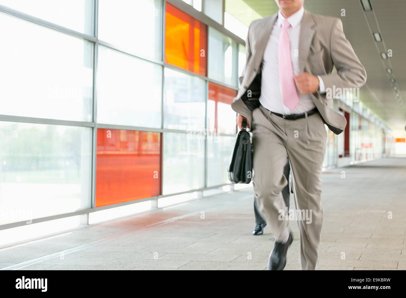 Midsection of businessmen rushing on railroad platform - Stock Image