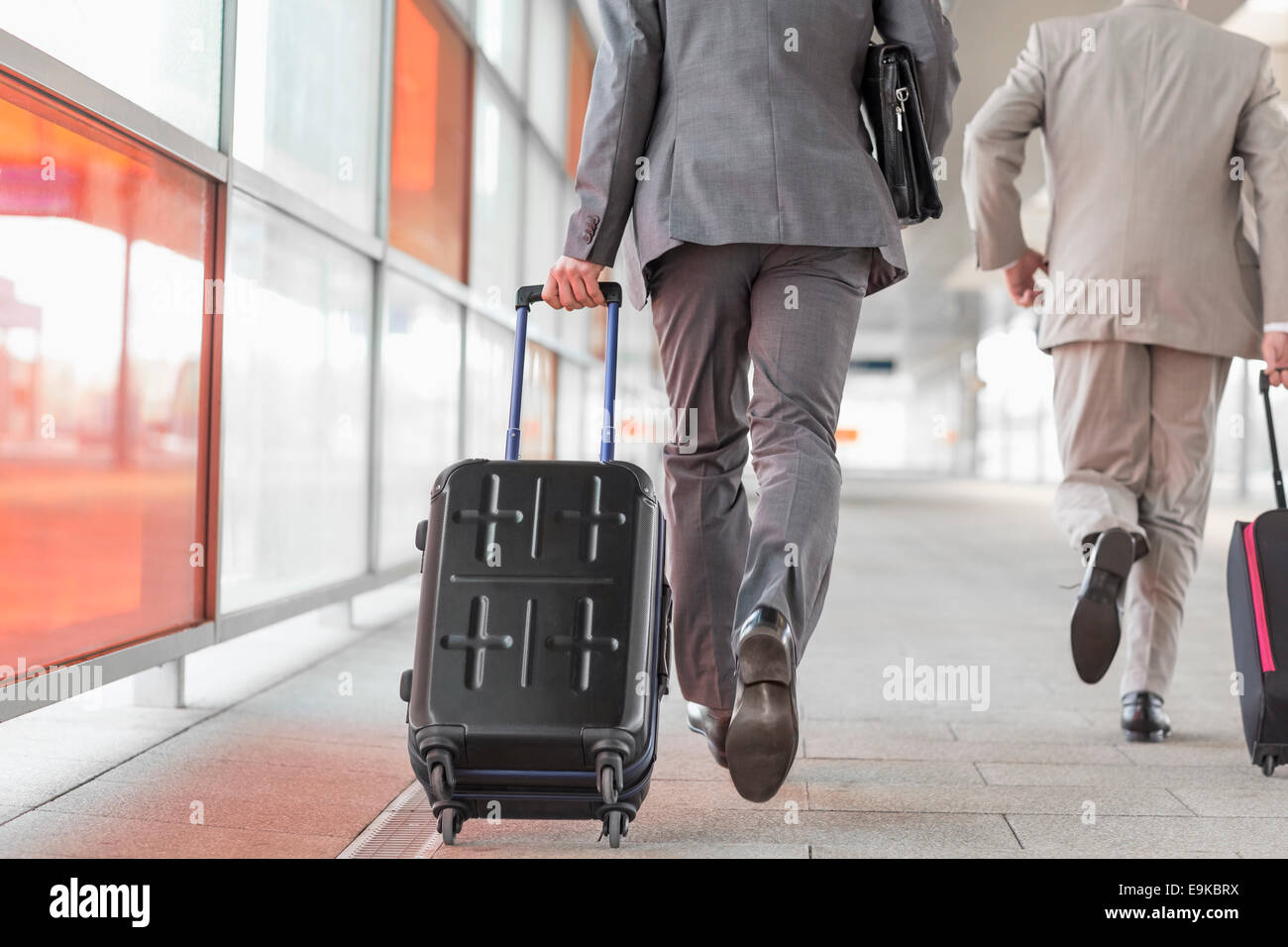 Rear view of businessmen with luggage running on railroad platform - Stock Image