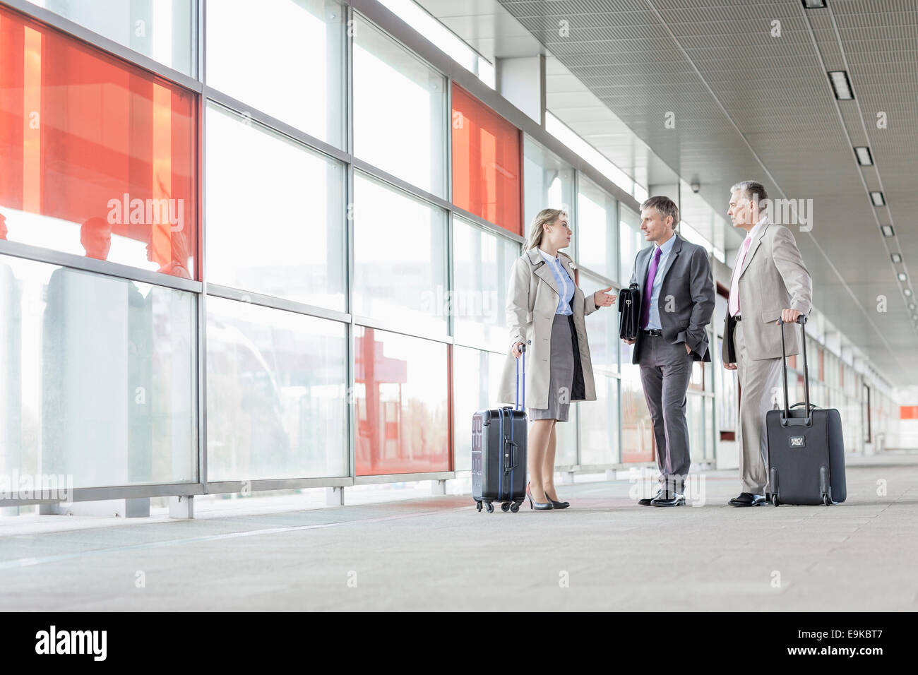 Full length of businesspeople with luggage talking on railroad platform - Stock Image