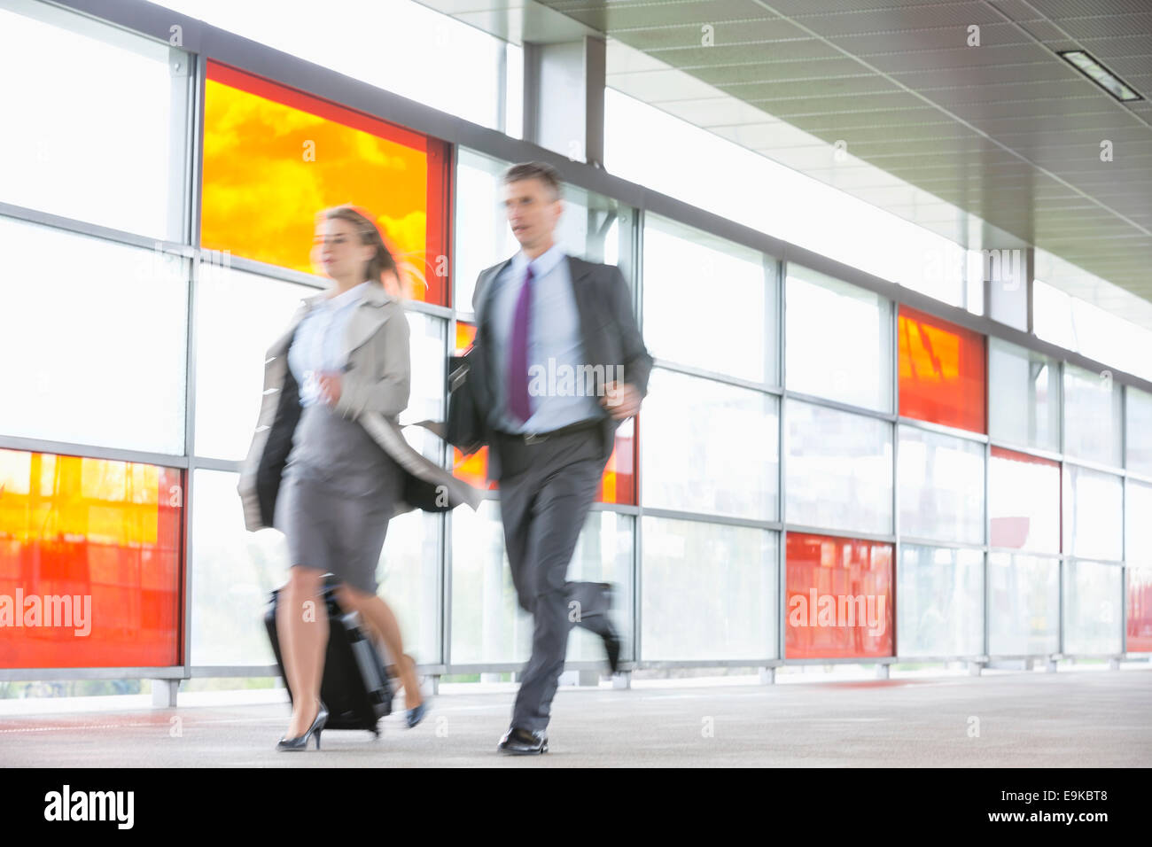 Businessman and businesswoman rushing in railroad station - Stock Image