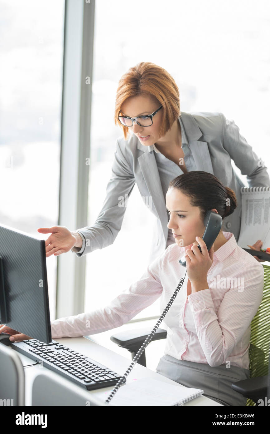 Businesswoman using landline phone while manager pointing towards computer in office - Stock Image