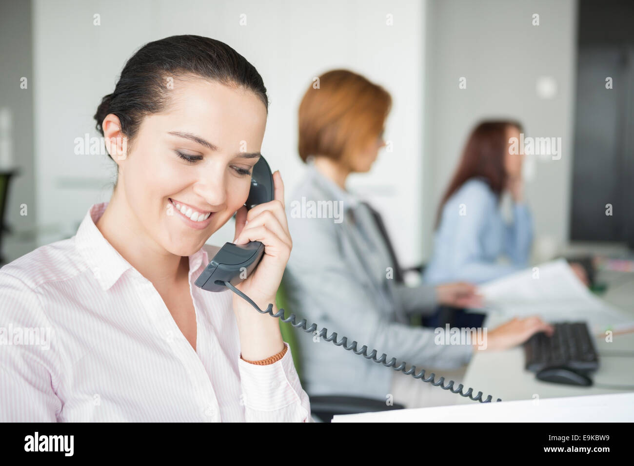 Smiling young businesswoman using landline telephone with colleagues in background at office - Stock Image