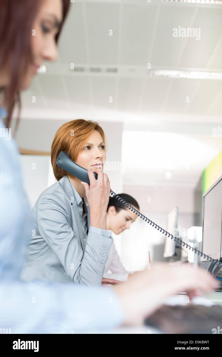 Young businesswoman using landline phone in office - Stock Image