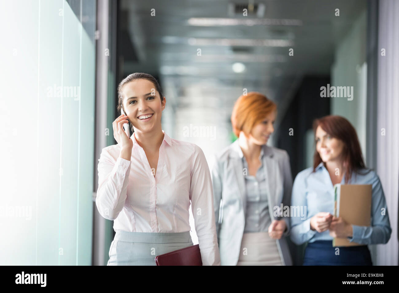Young businesswoman on call with colleagues in background at office corridor - Stock Image