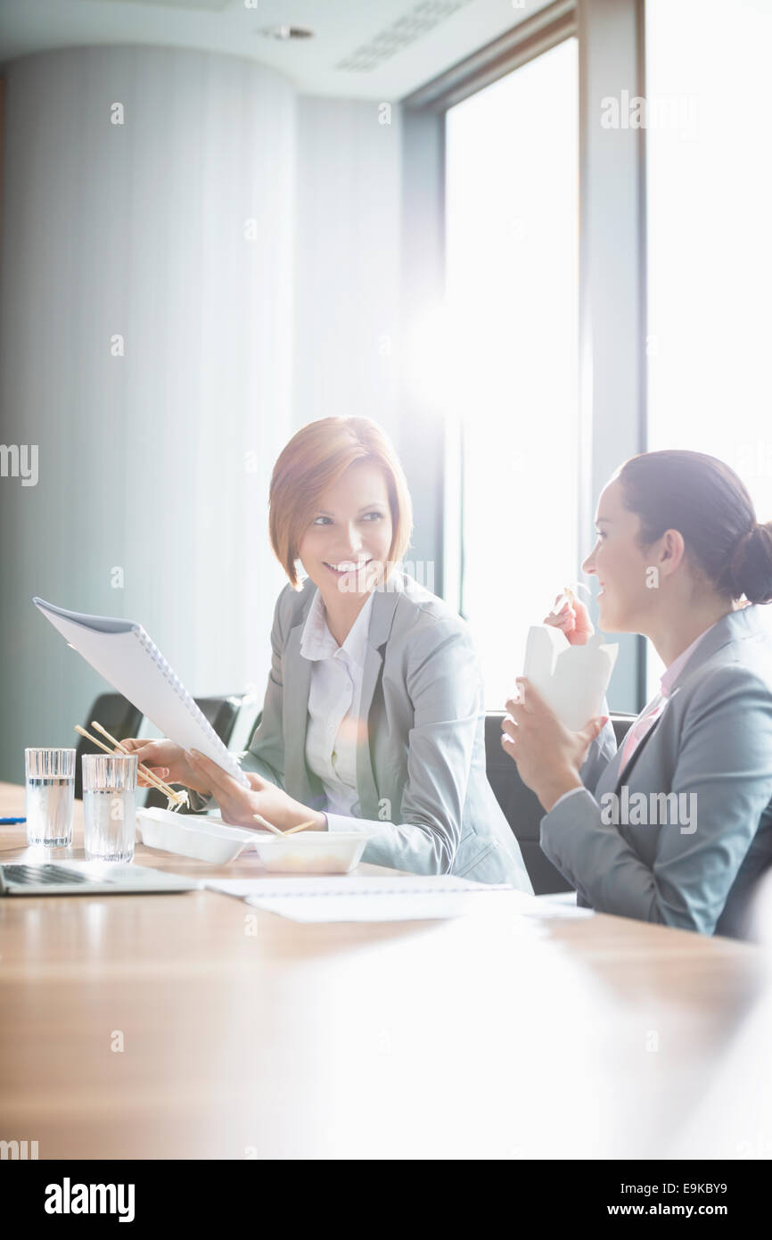 Young businesswomen working while having lunch at table in office - Stock Image