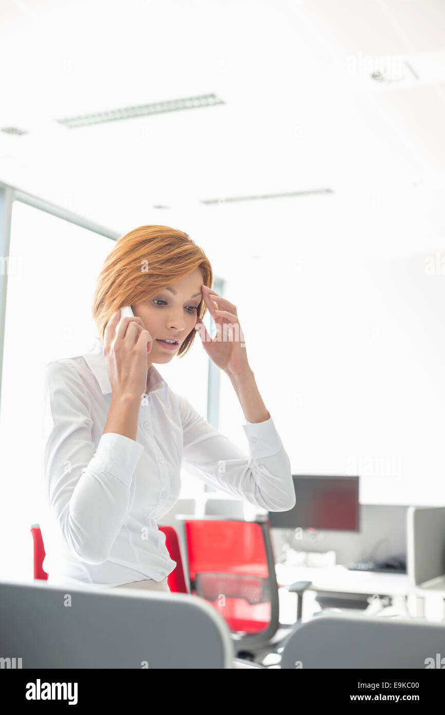 Shock businesswoman using cell phone in office - Stock Image
