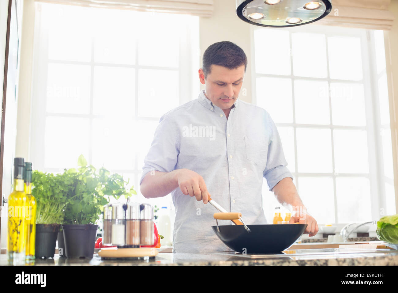 Middle-aged man preparing food in kitchen - Stock Image