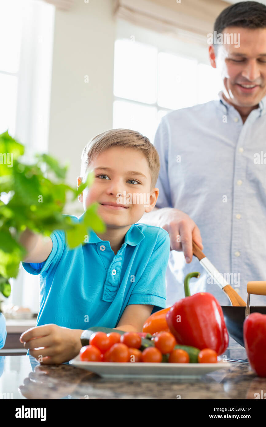 Smiling boy touching houseplant with father preparing food in kitchen - Stock Image