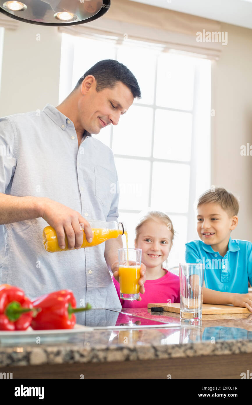 Father serving orange juice for children in kitchen - Stock Image