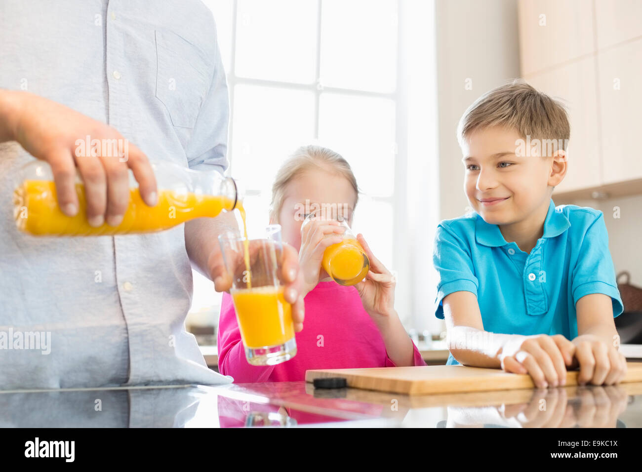 Midsection of father serving orange juice for children in kitchen - Stock Image