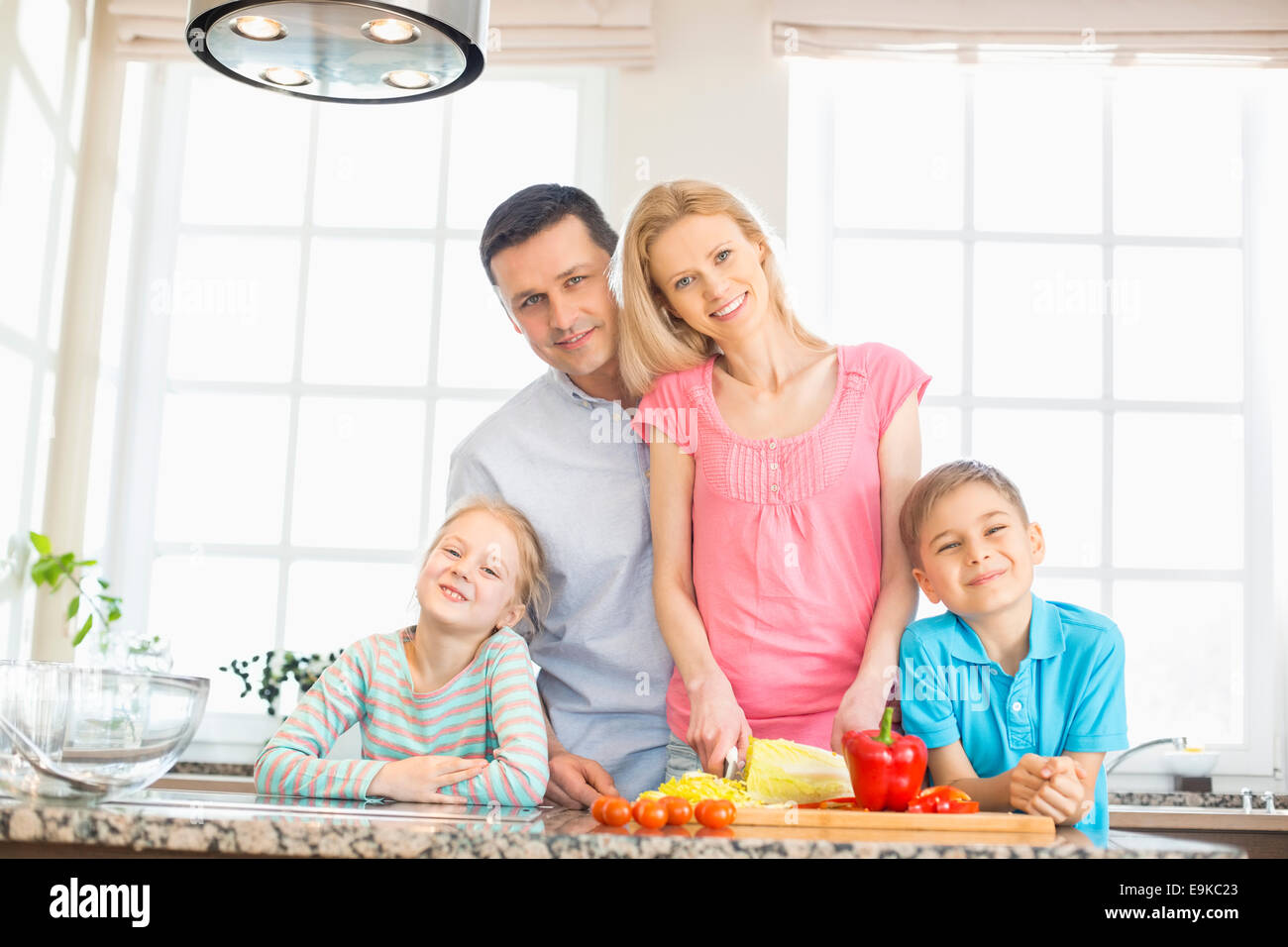 Portrait of happy family preparing food in kitchen - Stock Image