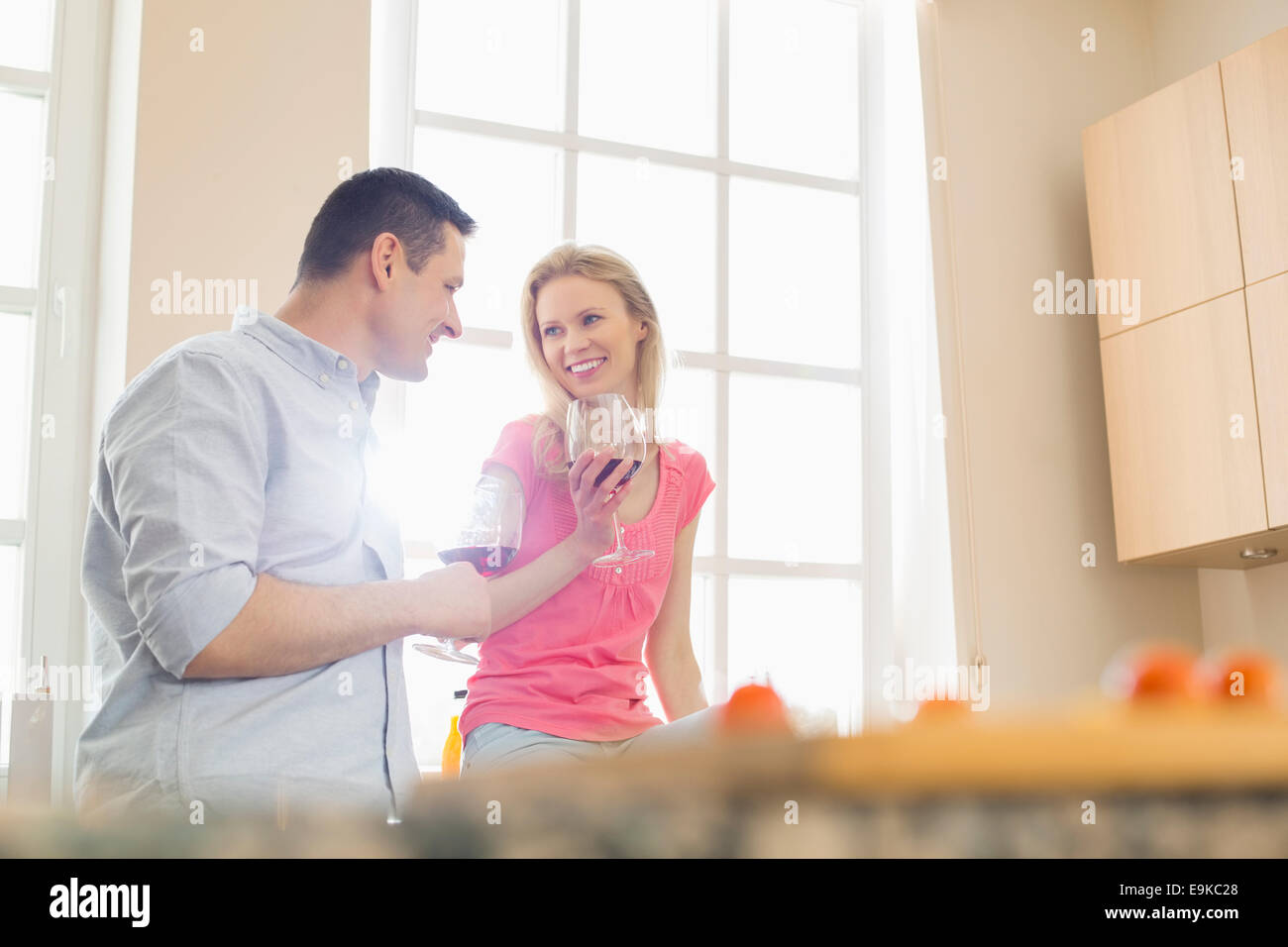 Happy couple drinking red wine in kitchen - Stock Image