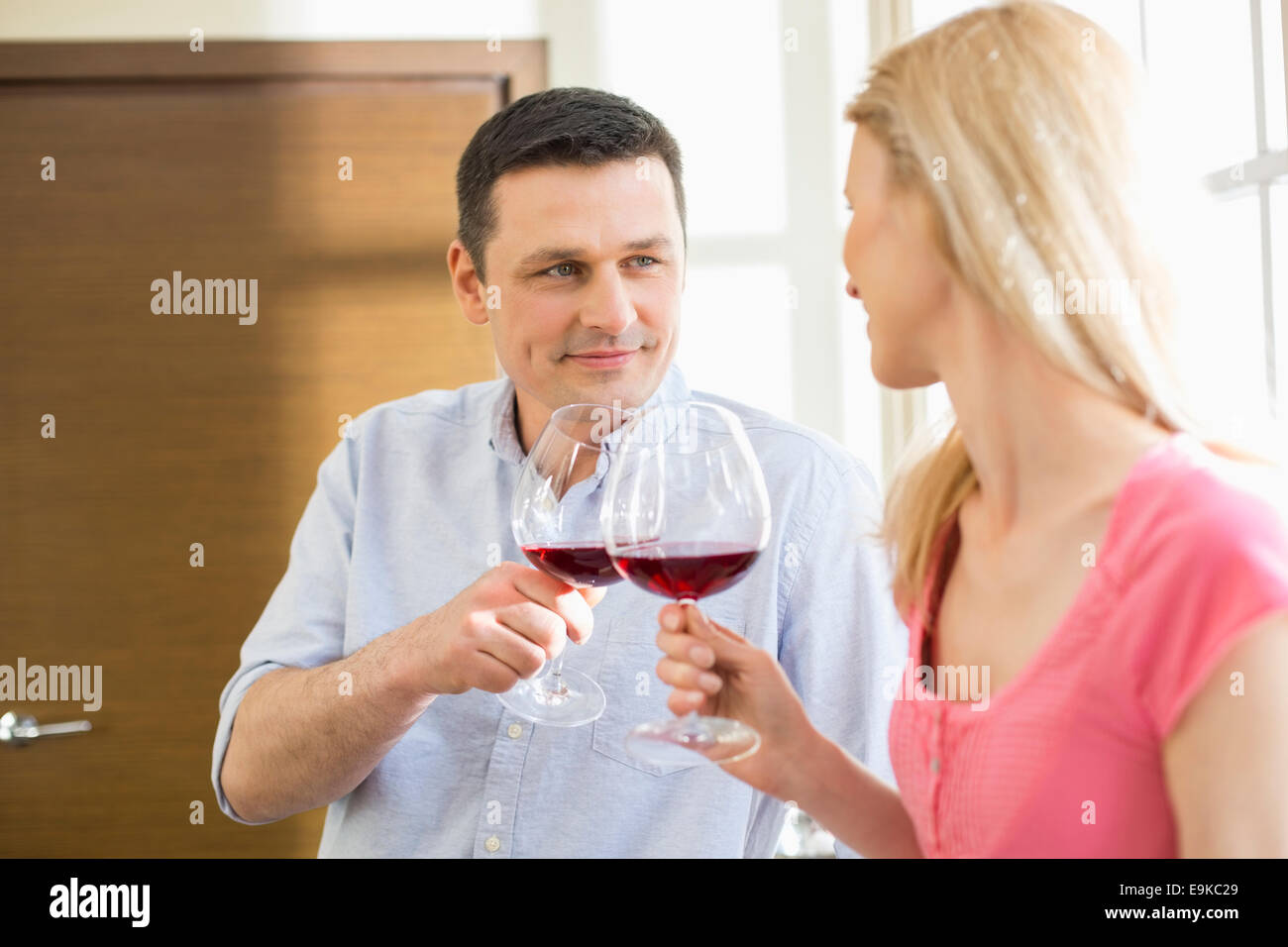 Couple toasting red wine glasses in kitchen Stock Photo