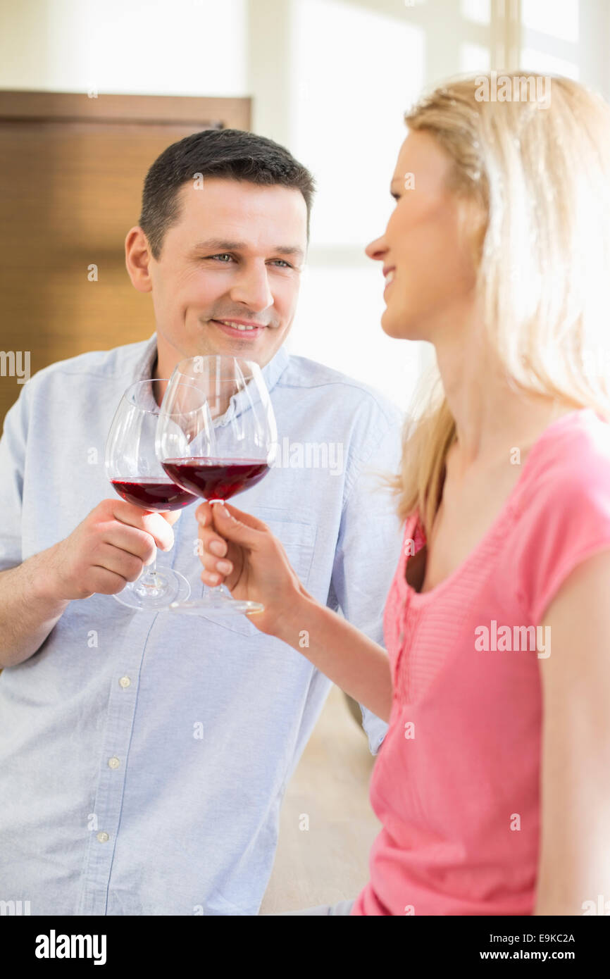 Happy couple toasting red wine glasses in kitchen - Stock Image