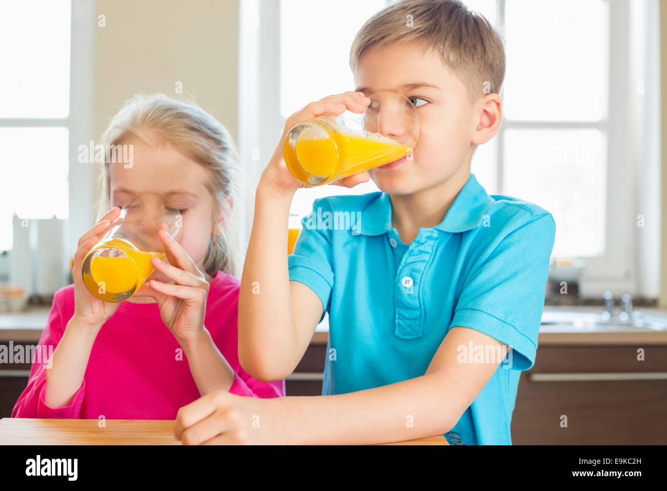 Siblings drinking orange juice in kitchen at home - Stock Image