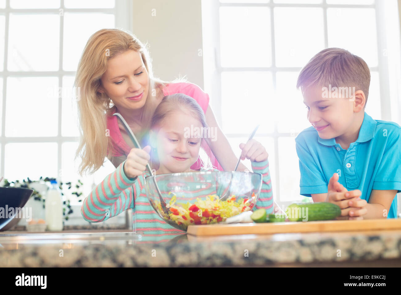 Family looking at girl mixing salad in kitchen Stock Photo