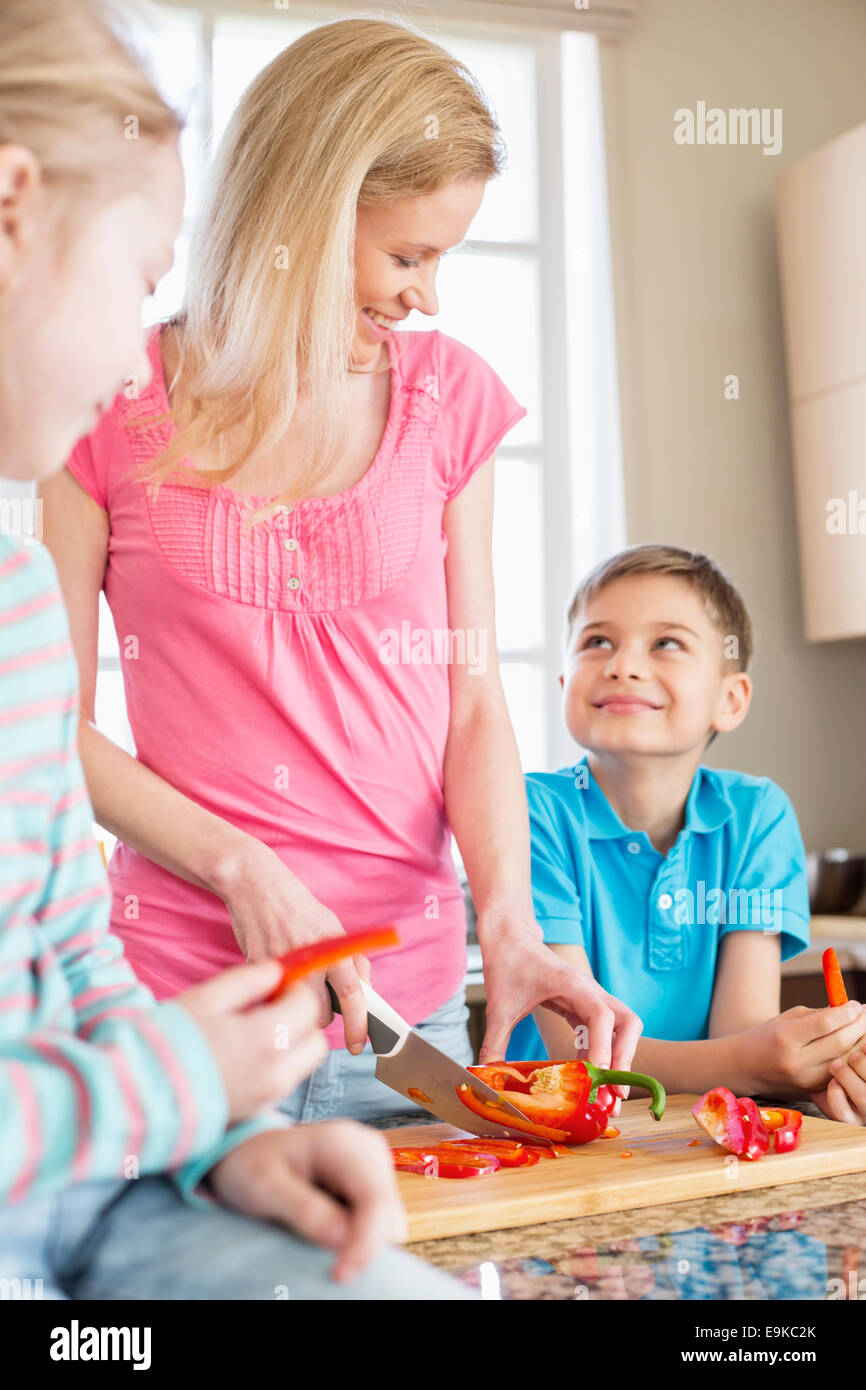 Happy woman chopping red bell pepper while standing with children in kitchen - Stock Image
