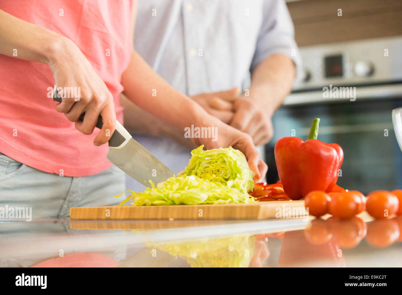 Midsection of woman chopping vegetables in kitchen with man standing in background - Stock Image