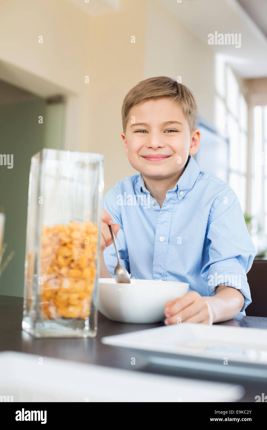 Portrait of smiling boy pouring corn flakes in bowl at home - Stock Image