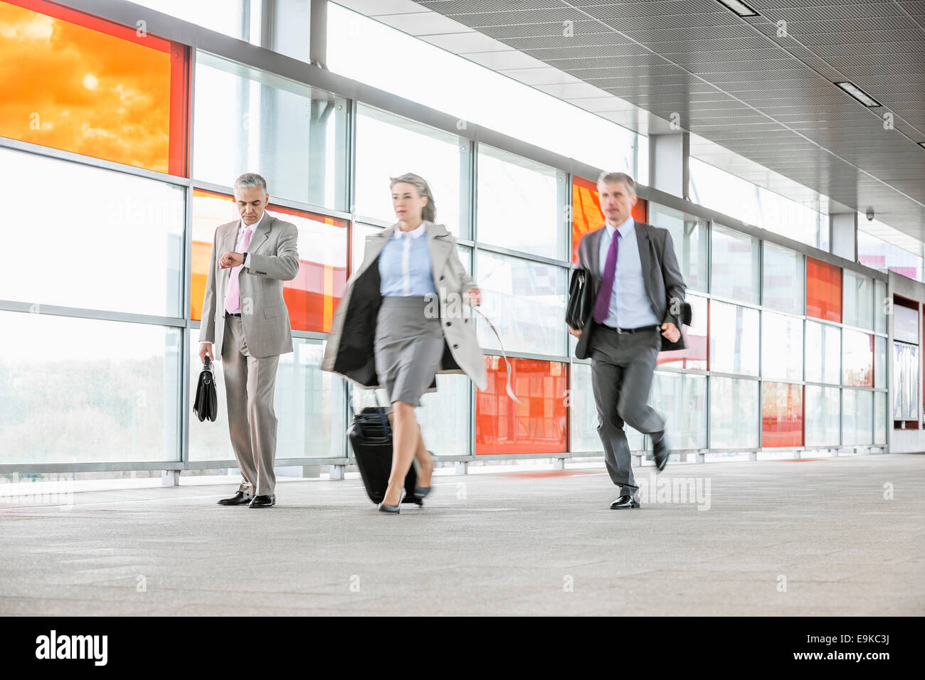 Full length of businesspeople rushing in railroad station - Stock Image