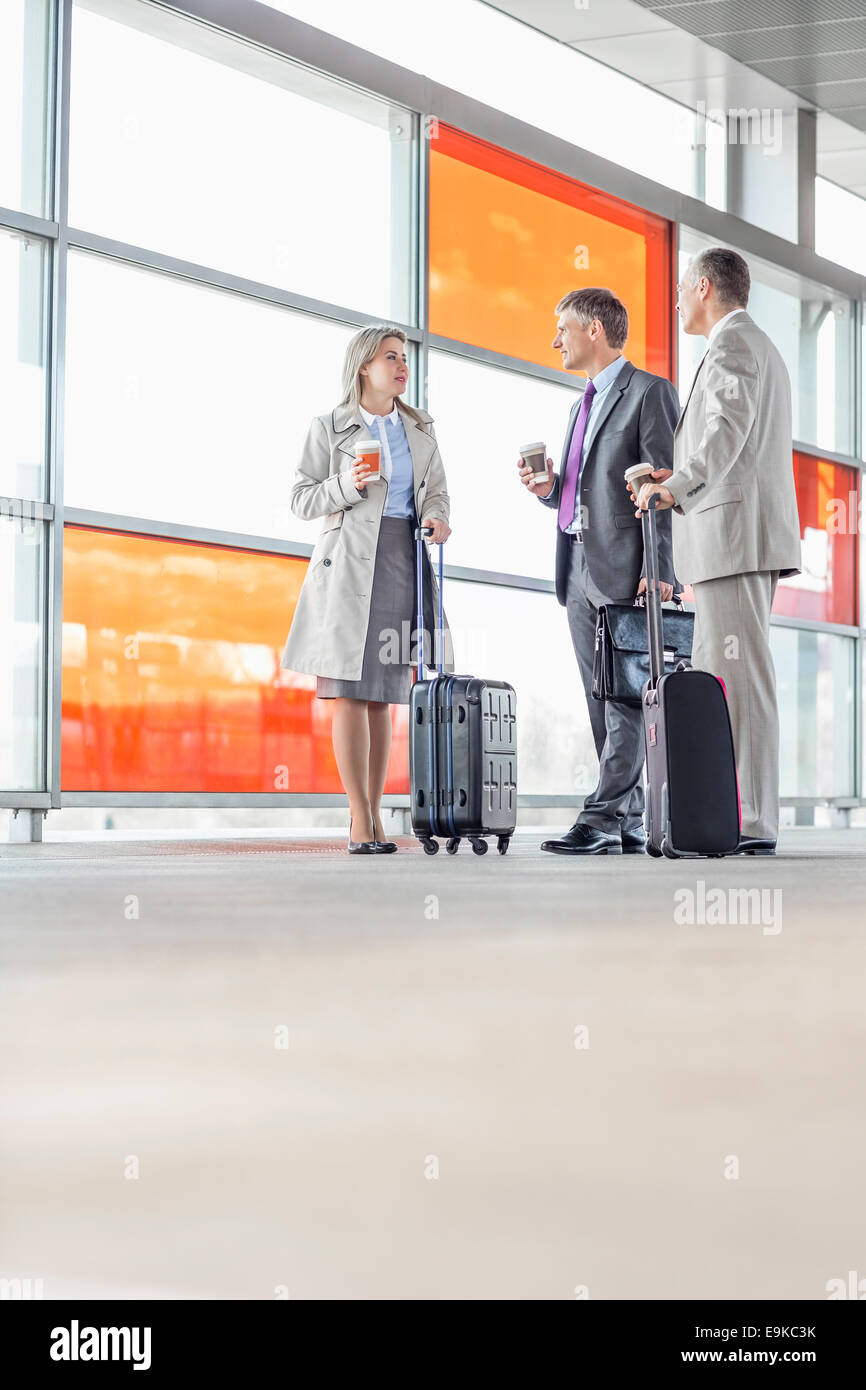 Full length of businesspeople talking on railroad platform - Stock Image