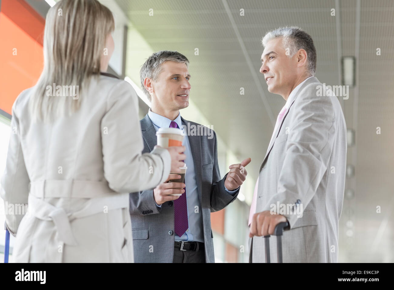 Businesspeople communicating on railroad platform - Stock Image