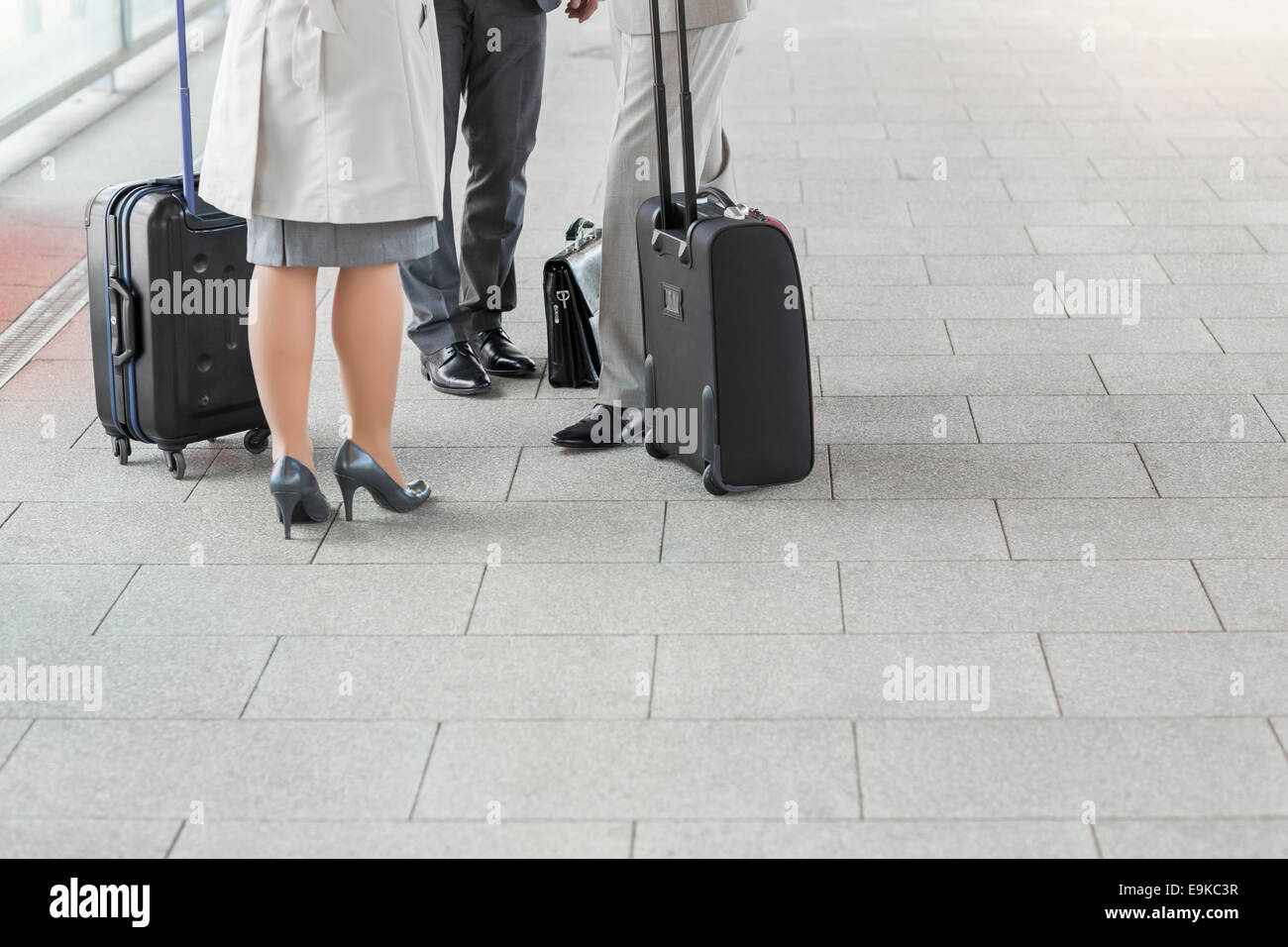 Low section of businesspeople with luggage standing on railroad platform Stock Photo