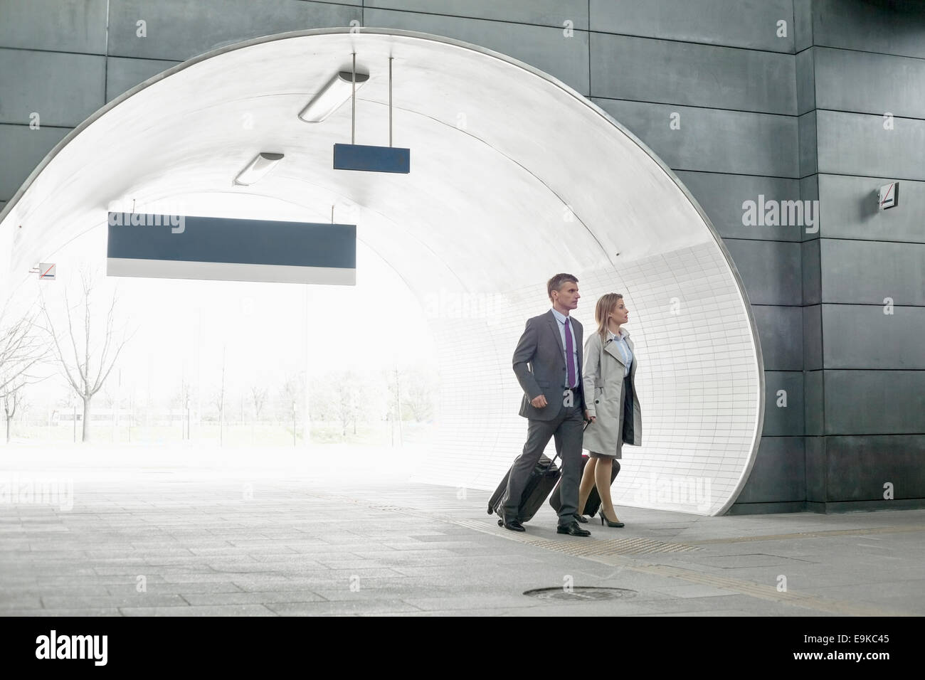 Businessman and businesswoman entering railroad station - Stock Image