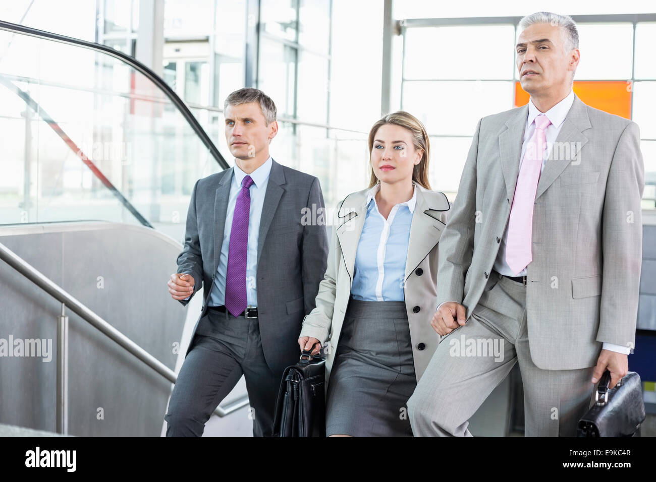 Businesspeople walking up stairs in train station Stock Photo