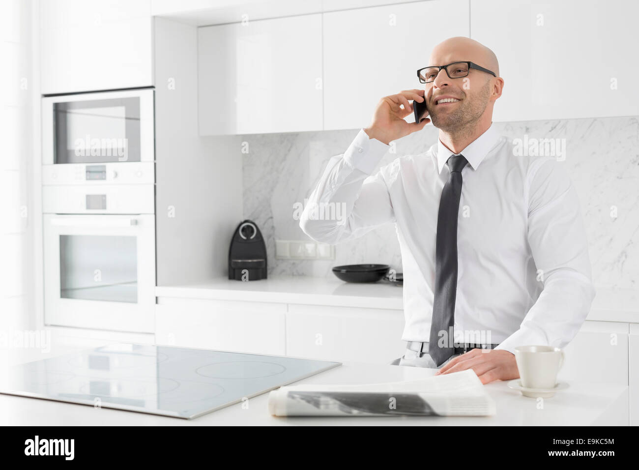 Mid adult businessman on call at kitchen counter - Stock Image