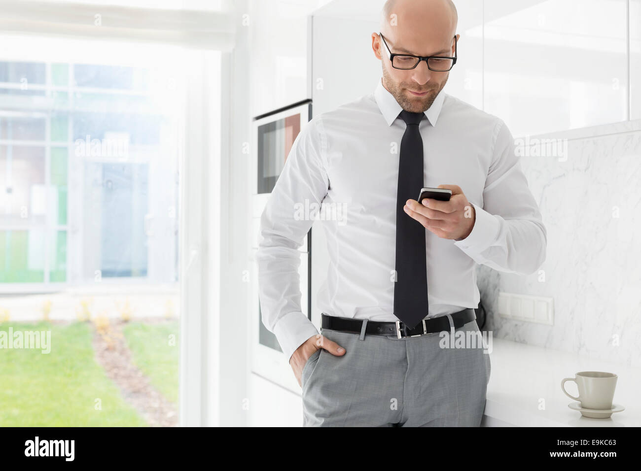 Mid adult businessman text messaging through smart phone at home - Stock Image