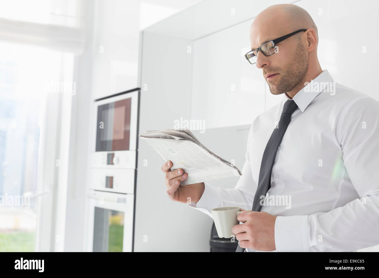 Mid adult businessman having coffee while reading newspaper at home Stock Photo