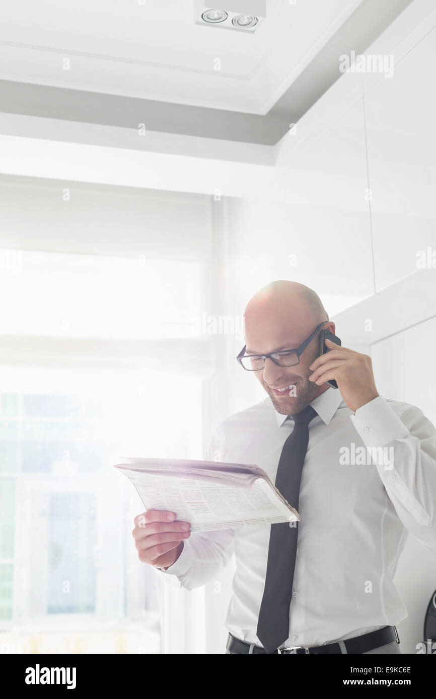 Happy businessman on call while reading newspaper at home - Stock Image