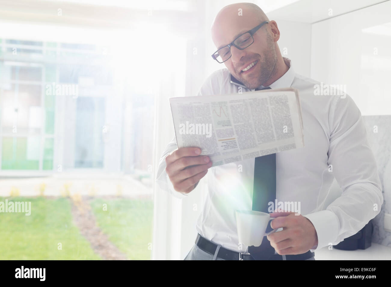 Mid adult businessman on call while holding newspaper and coffee cup at home - Stock Image