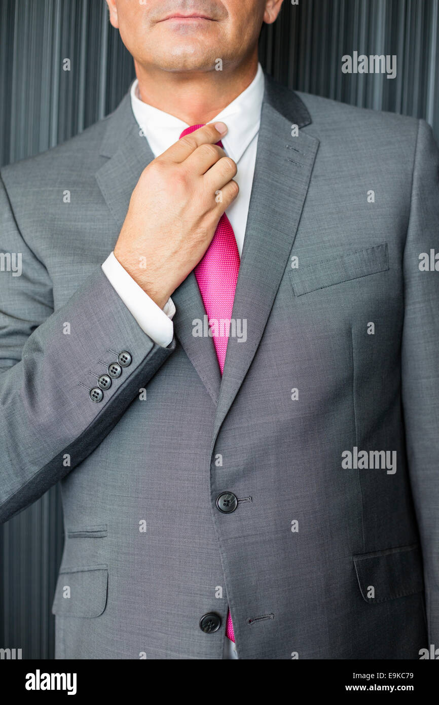 Midsection of mature businessman adjusting necktie - Stock Image