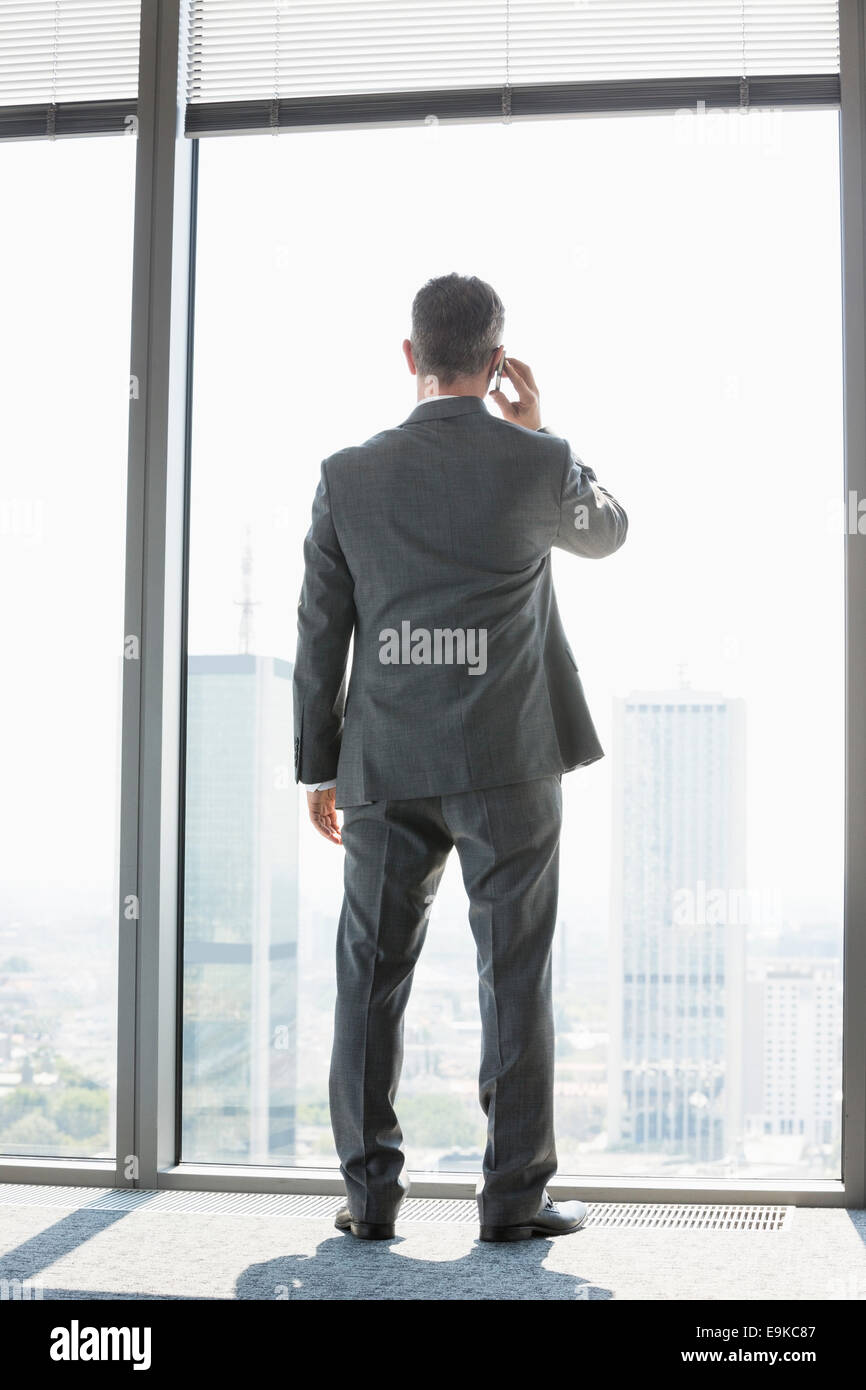 Full length rear view of mature businessman using cell phone white standing near window - Stock Image