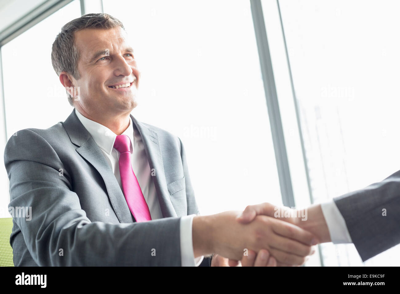 Smiling mature businessman shaking hands with partner in office - Stock Image