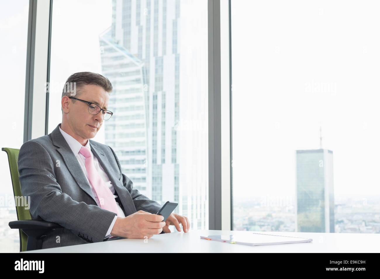 Mature businessman text messaging through cell phone near office window - Stock Image