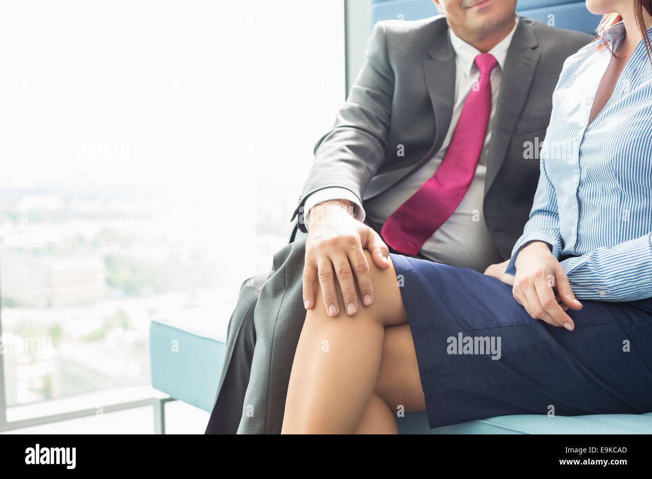 Midsection of businessman flirting with female colleague in office - Stock Image