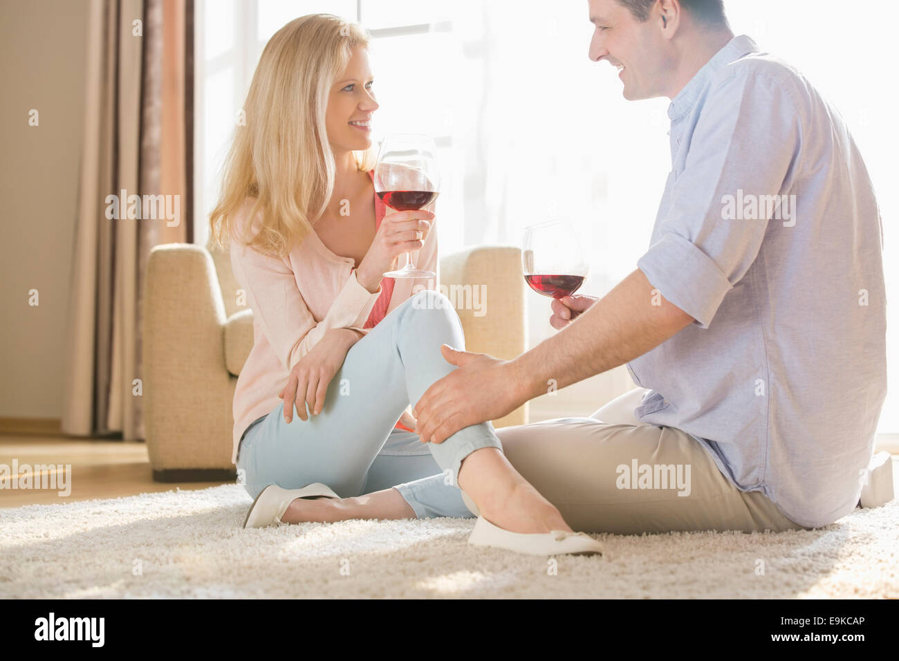 Loving couple looking at each other while drinking red wine at home - Stock Image
