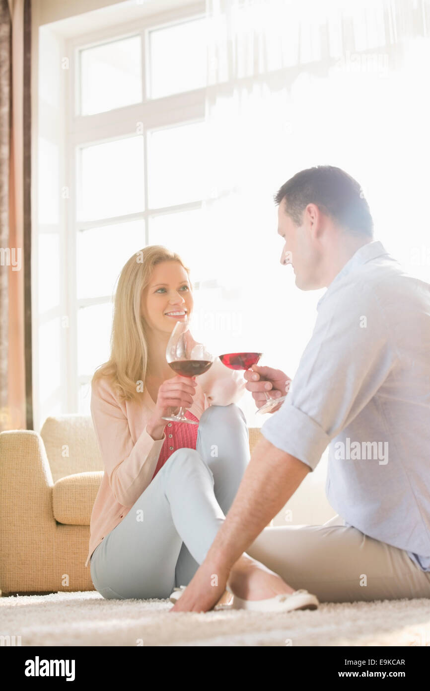 Happy couple looking at each other while having red wine at home - Stock Image