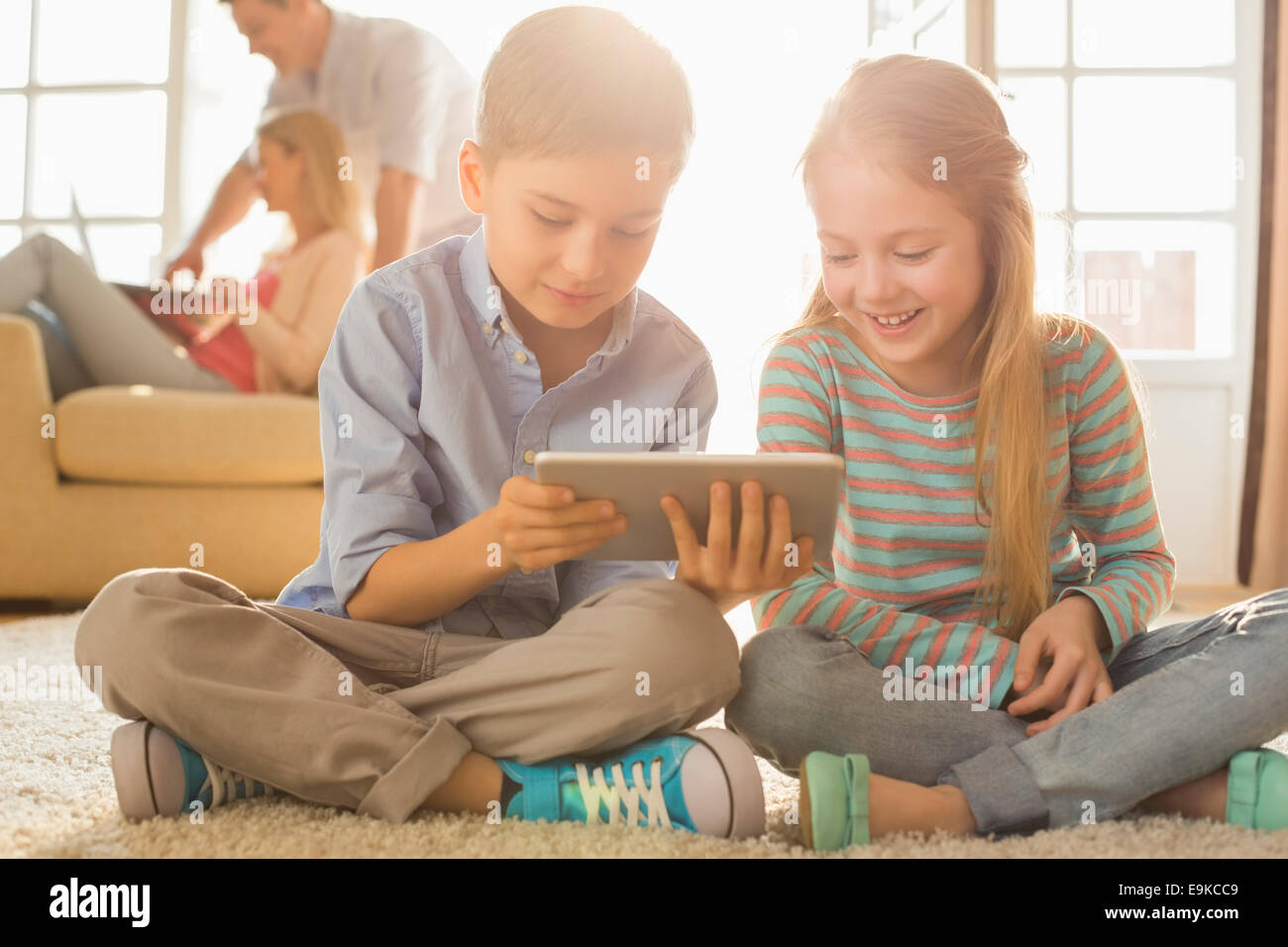 Happy siblings using digital tablet on floor with parents in background - Stock Image