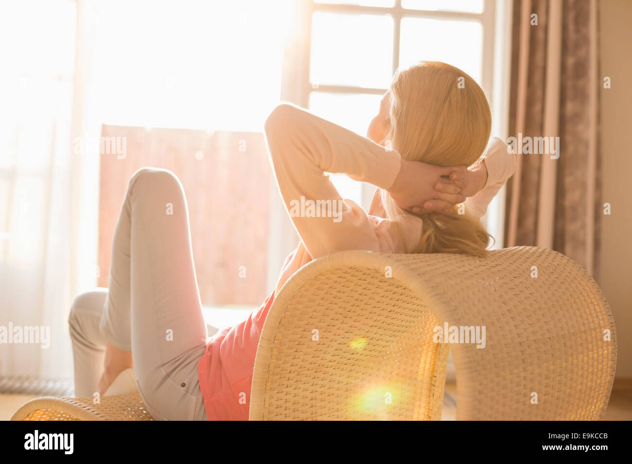 Rear view of woman relaxing on chair at home - Stock Image